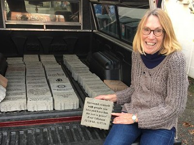 """Ann with a truck load of the 8"""" x 8"""" gray bricks."""